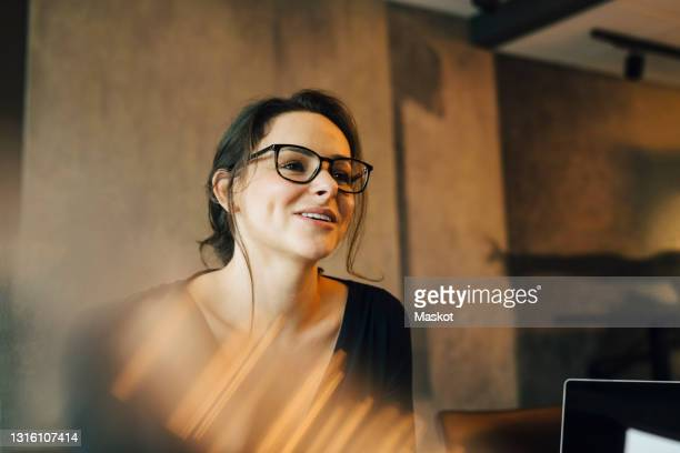 smiling female entrepreneur looking away in office - lawyer stock pictures, royalty-free photos & images
