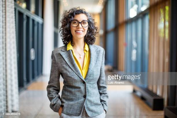 smiling female entrepreneur outside auditorium - zakenvrouw stockfoto's en -beelden