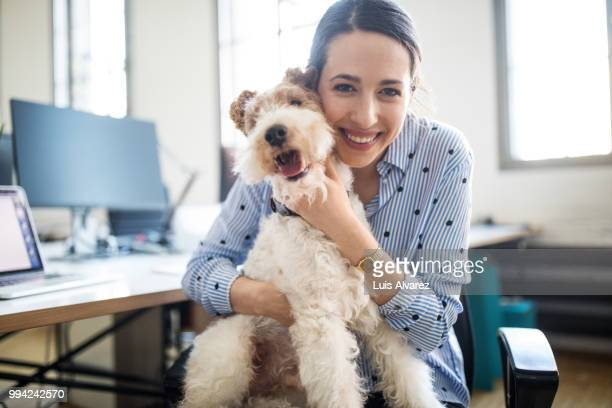 smiling female entrepreneur sitting with dog - pet owner stock pictures, royalty-free photos & images