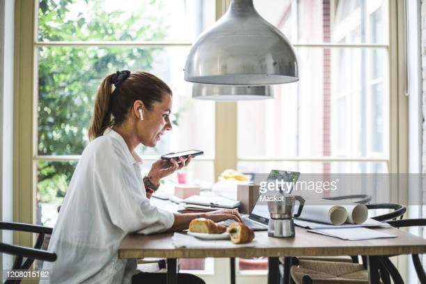 smiling female entrepreneur using laptop while talking through smart phone at home office - home office stock pictures, royalty-free photos & images