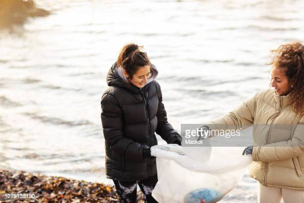 Smiling female environmentalists collecting microplastics against lake