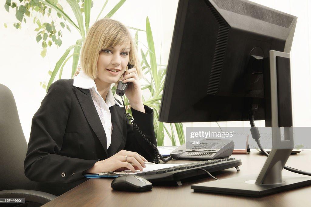 Smiling female executive talking on phone : Stock Photo