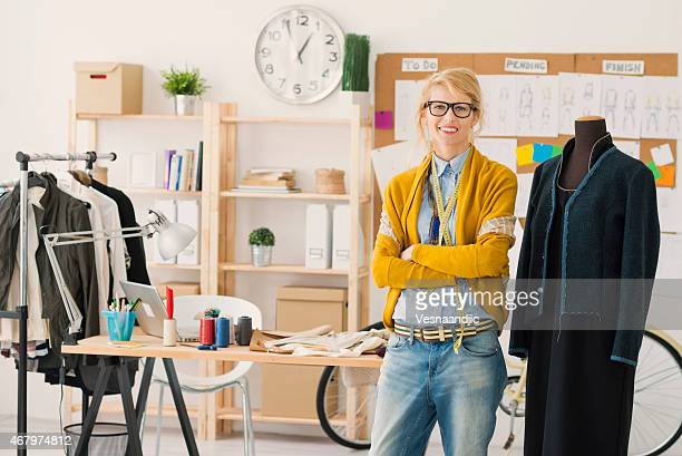 Smiling female fashion designer with arms crossed at studio
