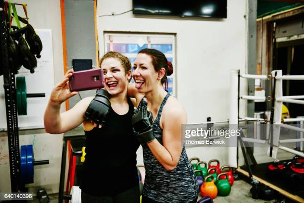 Smiling female fighters taking self portrait with smartphone after training session in gym
