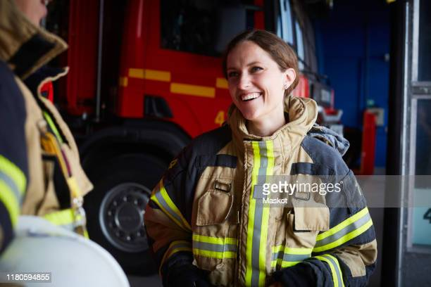 smiling female firefighter looking at coworker while communicating in fire station - 消防士 ストックフォトと画像