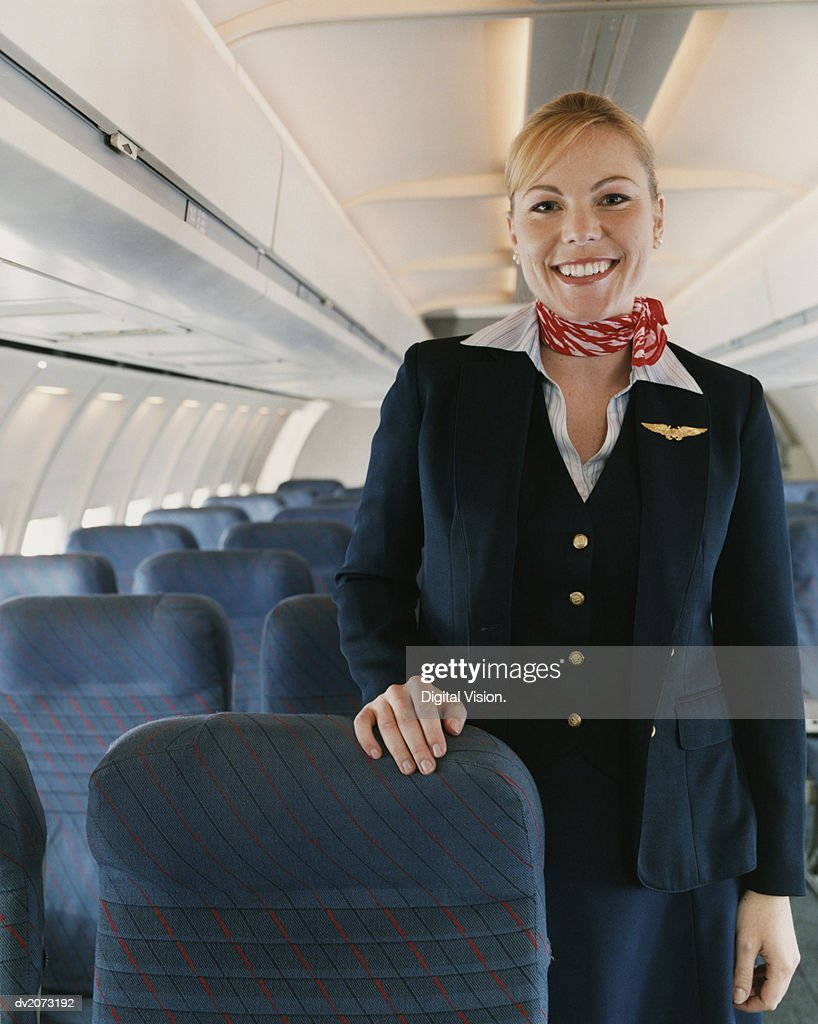 Smiling Female Flight Attendant Standing in the Cabin of a Plane : Stock Photo