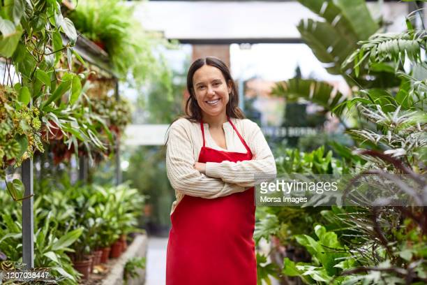 smiling female florist standing with arms crossed - three quarter length stock pictures, royalty-free photos & images