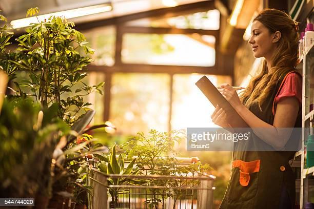 Lächelnde Frau blumenhändler Notizen in einem Gewächshaus.