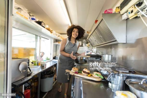 Smiling female food van worker making sandiches