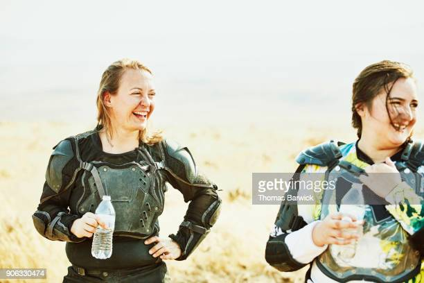 Smiling female friends drinking water while resting during desert dirt bike ride