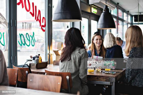 smiling female friends enjoying while sitting at dining table for brunch in restaurant - the brunch stock pictures, royalty-free photos & images