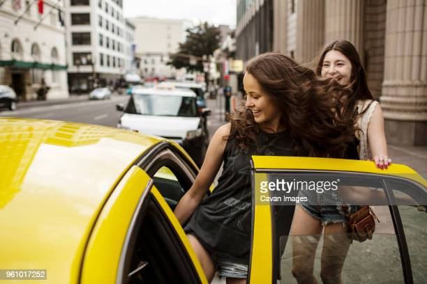 smiling female friends entering in taxi - entrata foto e immagini stock