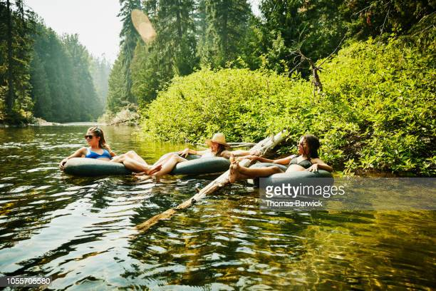 smiling female friends hanging out in inner tubes on river on summer afternoon - inflatable ring stock pictures, royalty-free photos & images