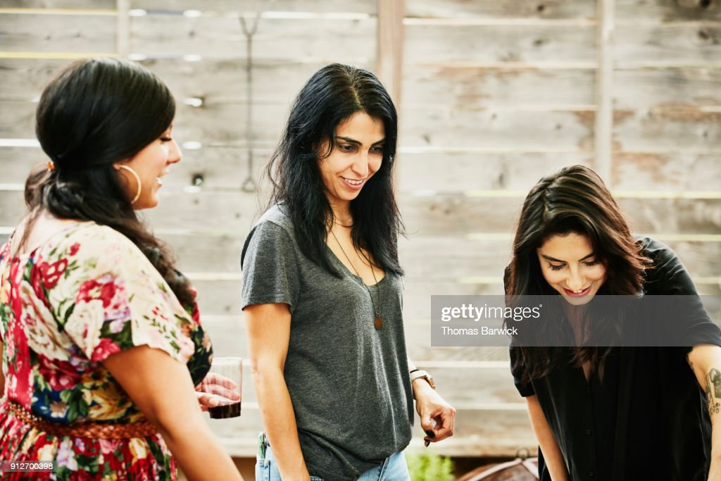 Smiling female friends hanging out together during backyard party : Foto de stock