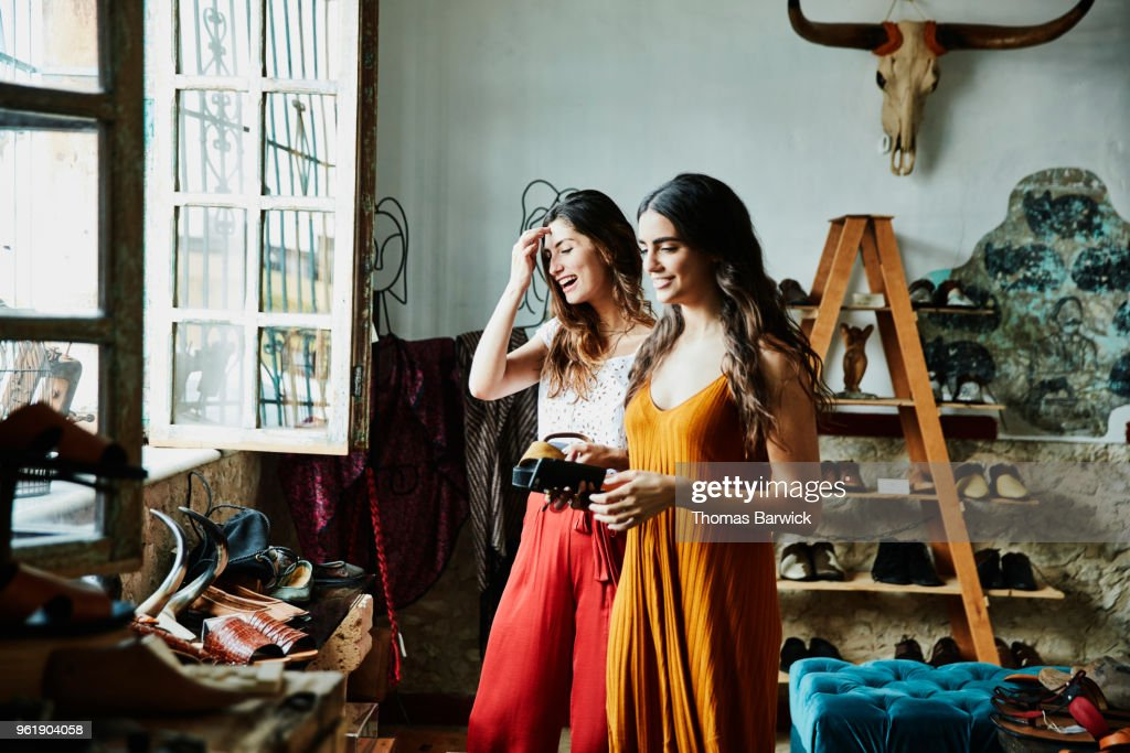 Smiling female friends in discussion while shopping in shoe boutique : Stock Photo