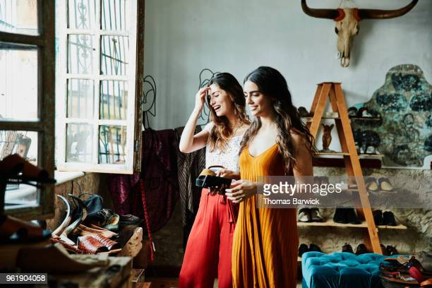 Smiling female friends in discussion while shopping in shoe boutique