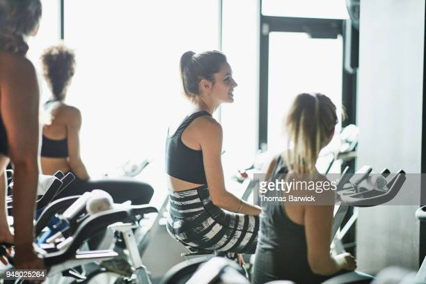 Smiling female friends in discussion while warming up on fitness bikes before workout in cycling studio