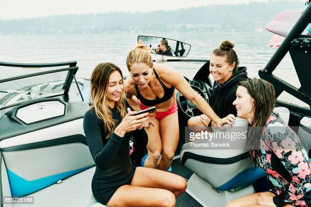 Smiling female friends on boat watching video on smartphone in between wakeboarding sessions