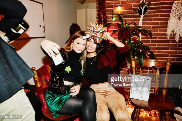 smiling female friends posing for selfie with bow over their heads during holiday party in home - 20 29 anos imagens e fotografias de stock