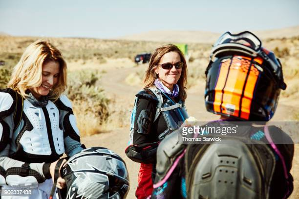 Smiling female friends preparing for dirt bike ride in desert