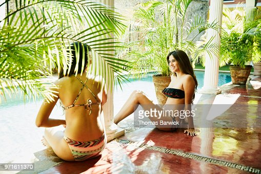 Smiling female friends relaxing by edge of pool at outdoor spa