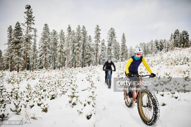smiling female friends riding fat tire bikes on snow covered trail - sólo con adultos fotografías e imágenes de stock