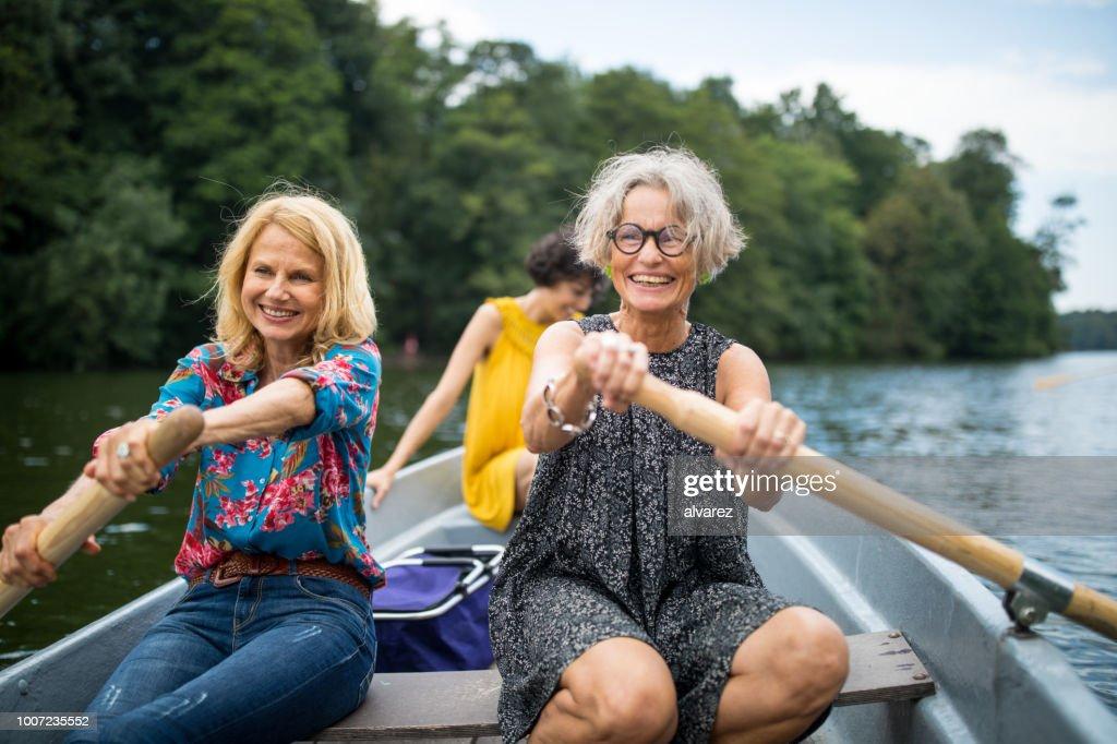 Lachende vriendinnen roeiboot in lake : Stockfoto