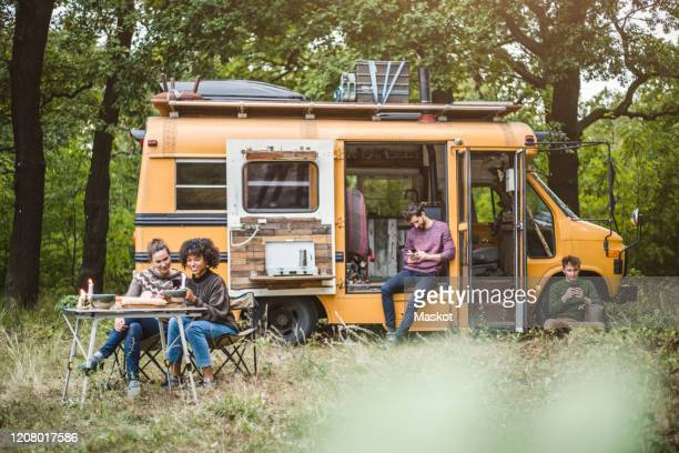 smiling female friends sitting at table while men using smart phones during camping in forest - outdoor pursuit stock pictures, royalty-free photos & images