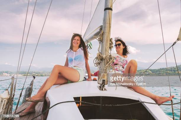 Smiling Female Friends Sitting In Yacht On River Against Sky