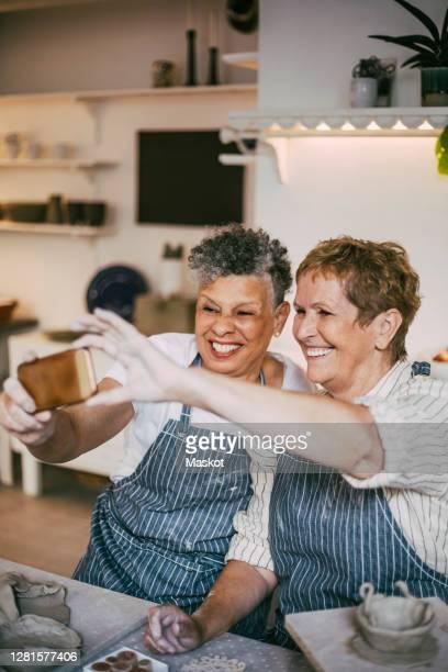 smiling female friends taking selfie through smart phone in workshop - disruptaging foto e immagini stock