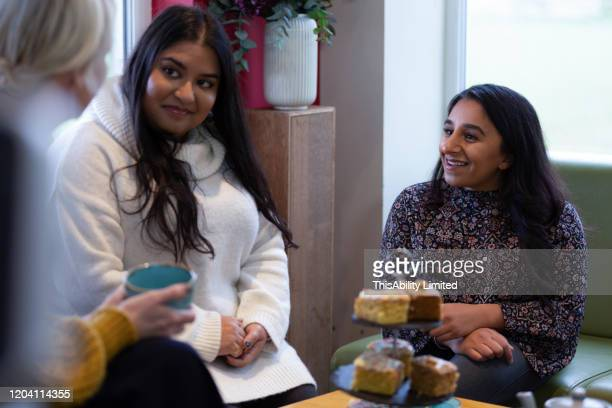 smiling female friends talking in cafe - disabilitycollection stock pictures, royalty-free photos & images