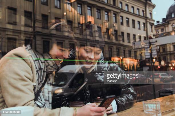 smiling female friends using mobile phone while sitting in cafe seen through window - city life stockfoto's en -beelden