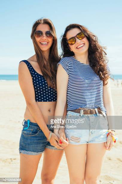 Smiling Female Friends Wearing Sunglasses While Standing At Beach
