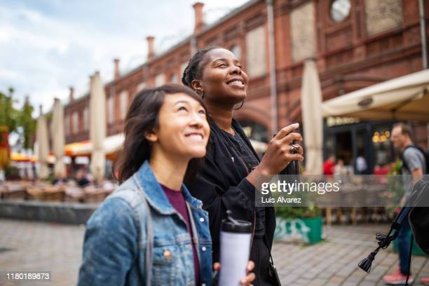 smiling female friends with drinks walking in city - city break stock pictures, royalty-free photos & images