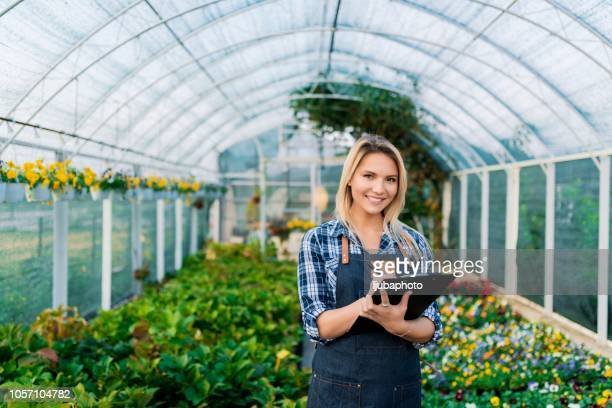 Smiling female gardener holding clipboard by flowers in greenhouse