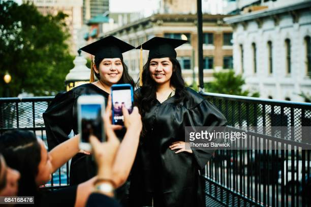 Smiling female graduates having pictures taken by family during celebration meal on restaurant deck