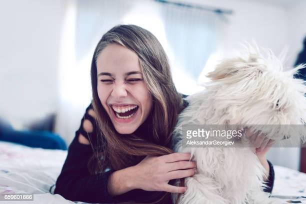 Sourire féminin vu plaisir avec son chien caniche dans le lit