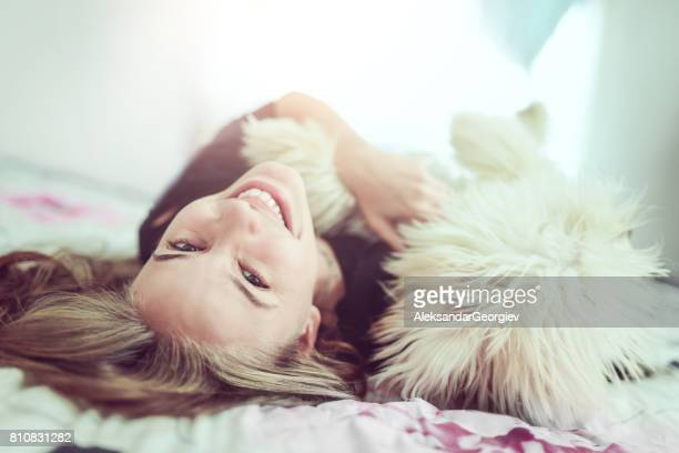Smiling Female Having Fun with her Poodle Dog in Bed