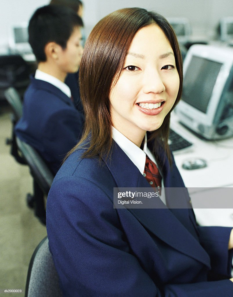 Smiling Female High School Student Sitting in a Computer Classroom : Stock Photo