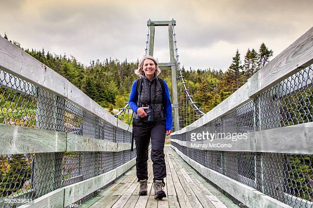 smiling female hiker crossing suspension bridge - murray mccomb stock pictures, royalty-free photos & images