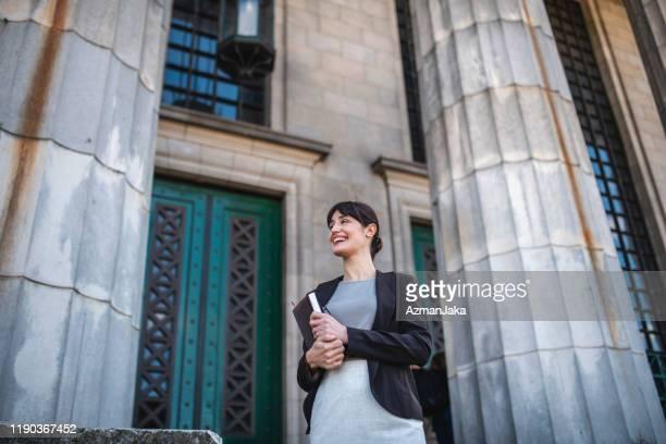 smiling female hispanic law student at entrance to school - lei imagens e fotografias de stock