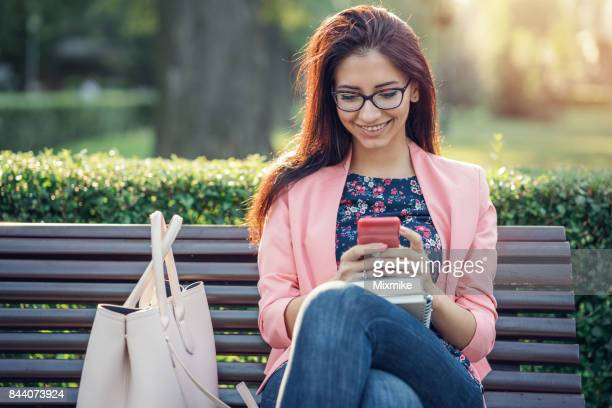 smiling female in the park chatting on her phone - candid forum stock pictures, royalty-free photos & images