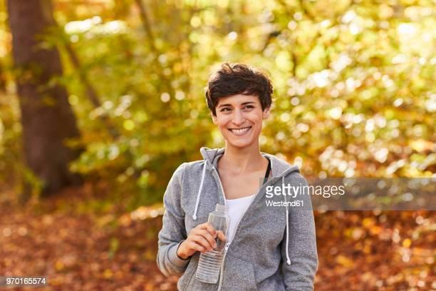 smiling female jogger with water bottle - desempenho atlético - fotografias e filmes do acervo