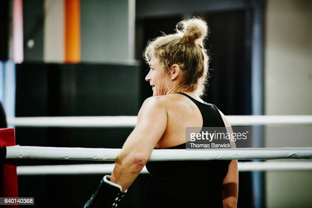Smiling female kickboxer resting during training session in ring