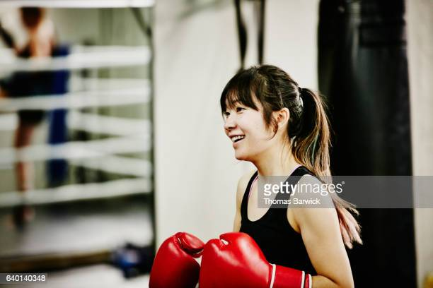 Smiling female kickboxer working out in fighting gym