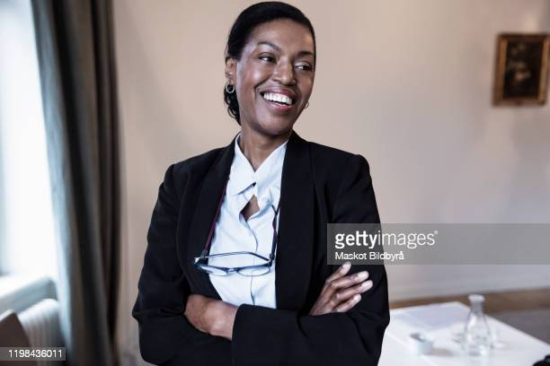 smiling female law professional with arms crossed standing at law firm - lawyer stock pictures, royalty-free photos & images