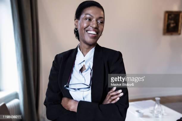 smiling female law professional with arms crossed standing at law firm - advogado - fotografias e filmes do acervo