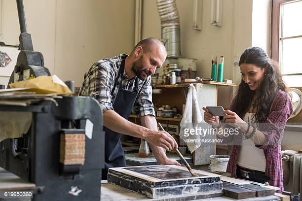 Smiling female lithography worker photographing her partner