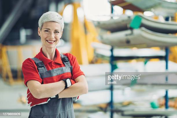 lächelnde mechanikerin - weiblichkeit stock-fotos und bilder