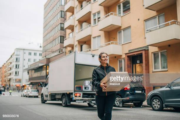 Smiling female messenger carrying box while walking in city